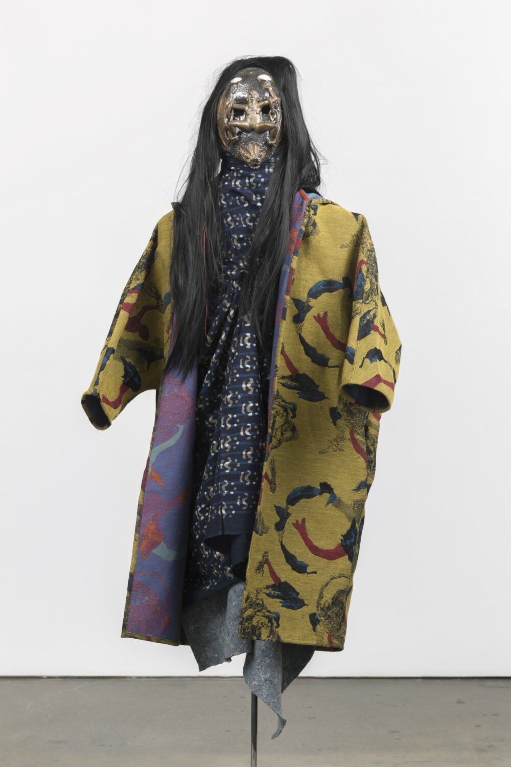 A figure or mannequin wearing a patterned yellow fabric jacket and a long patterned blue scarf, a black wig and a glazed ceramic mask