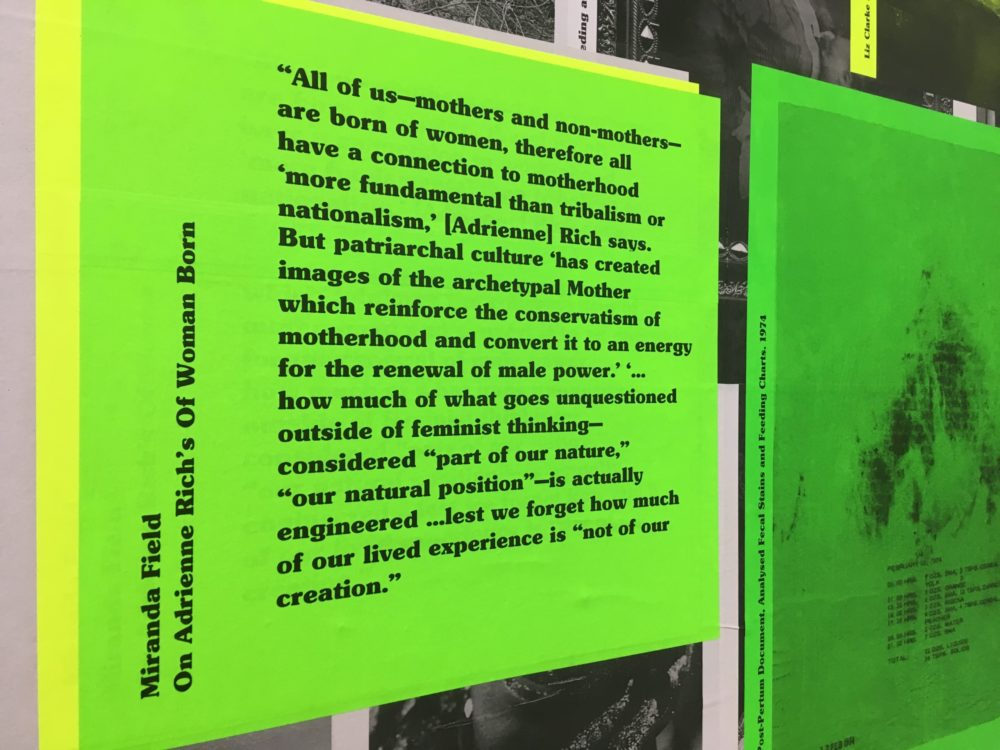 A neon green poster, pasted to a wall, with black bold serif text that reads: