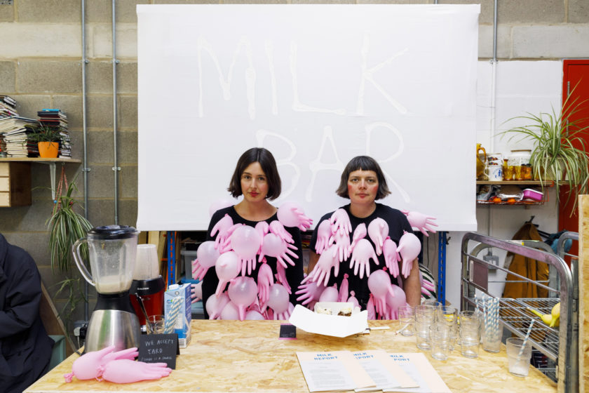 In an industrial studio setting, two women with bobbed brown hair sit in front of the camera, not smiling. They are wearing a matching outfit of a black t shirt adorned with pink plastic gloves that have been inflated. Behind them is a large sign with MILK BAR written on it. In front of them is a table with glasses, a food blender, straws, and papers.