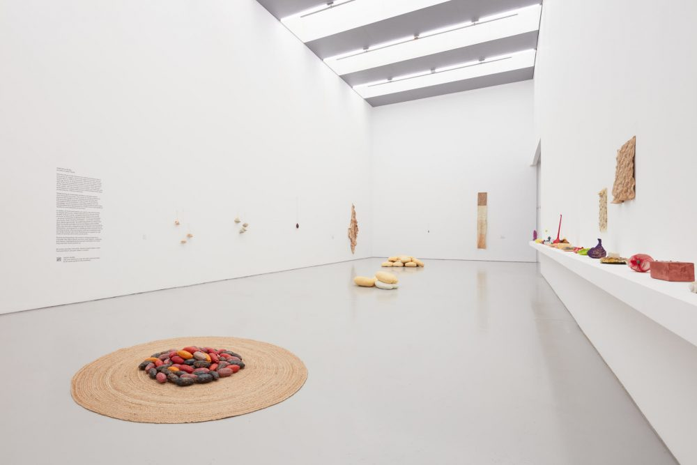A wide angle view of Veronica Ryan's exhibition Along a Spectrum at Spike Island, a gallery space filled with light and colourful sculptures and objects positioned on the gallery floor and walls