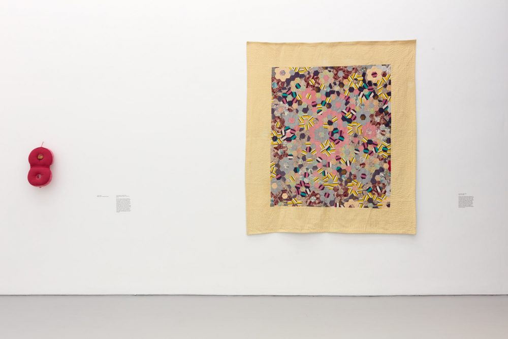 A photograph of two works by Veronica Ryan installed on a white gallery wall, including: Untitled (2019) Medical cushion, orange peel, thread and Safe Spaces (1988-2019) Fabric, ink, thread