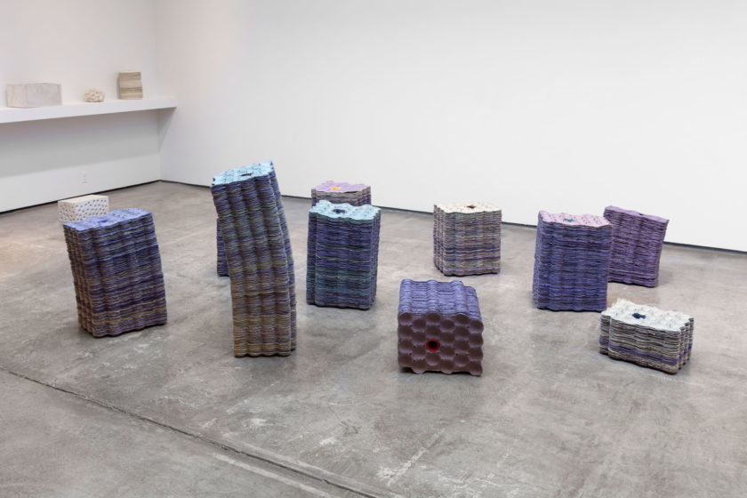 Various stacks of lilac coloured avocado trays on a concrete gallery floor. The taller stacks are slightly leaning. On the distant white gallery wall is a shelf with a variety of cream coloured objects.