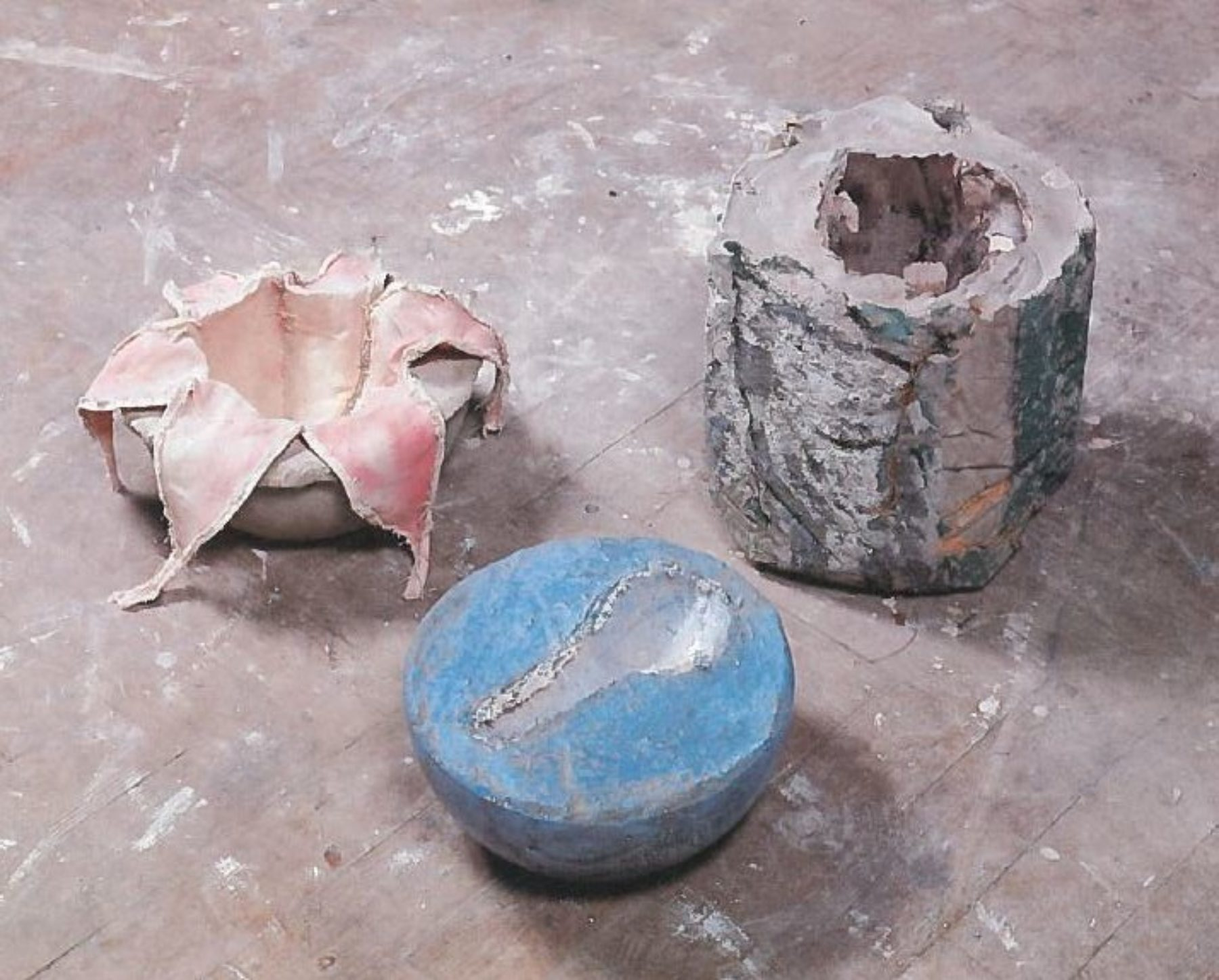 Photograph of three small sculptures placed on a grey, well worn floor. The sculptures are cast concrete - the first is round with a flower shape emerging from the centre. On the right, a cylindrical form with a central hole, and the third form is a bowl shape, coloured blue, with a key shape removed from the centre.