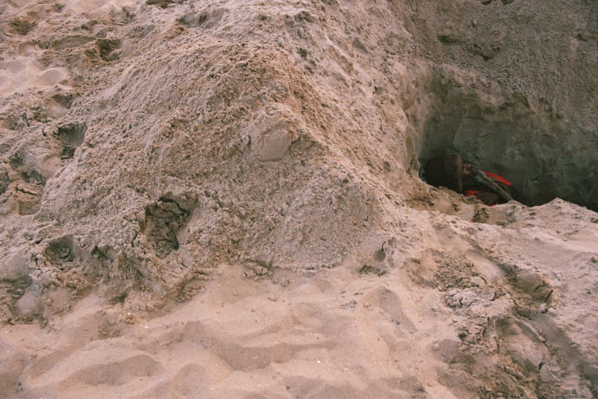 A photograph of a man down a hole on a sandy beach, the top of his head is just visible.