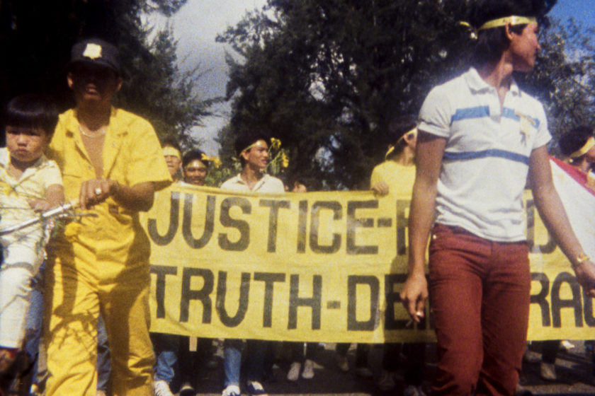 A grainy photograph of a protest. People in the background are wearing yellow headbands and holding yellow flyers. They are also displaying a large banner where the words