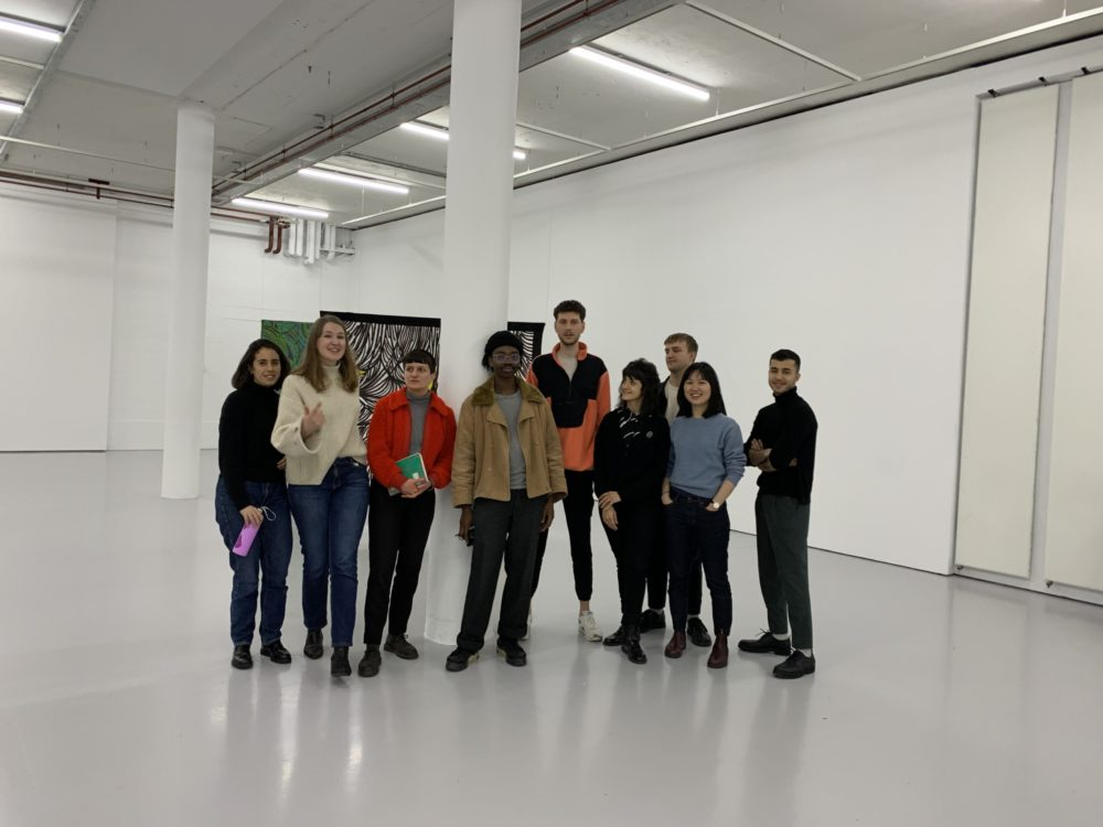 Eight participants stand in our gallery with a member of our curatorial team.