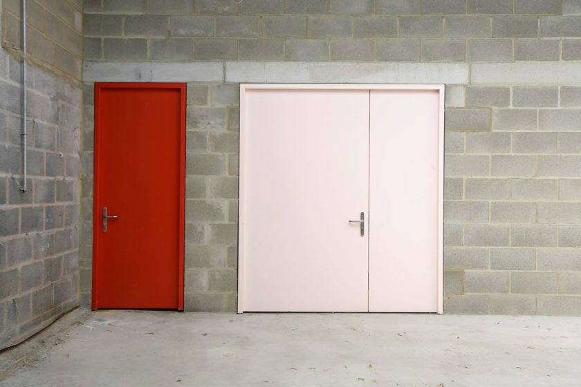 A photograph of a grey breeze block wall, featuring two closed doors - the left door is red and the right door is pink.