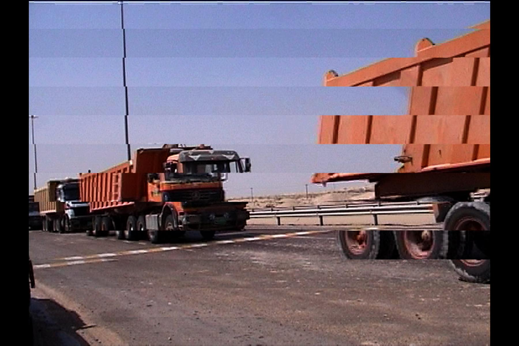 Large red trucks drive across the shot. The image has been manipulated so that strips of the image are offset from one another.