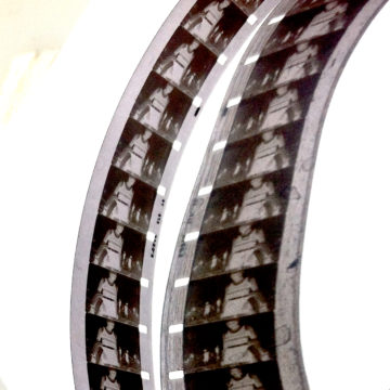Vicky Smith's work 'jinty', A photograph of two strips of 16mm black and white film reel, curving over a white background