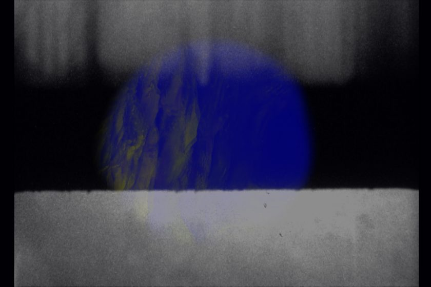 Production still: A blue circle sits behind a white rectangle with white rectangular shadows at the top of the frame
