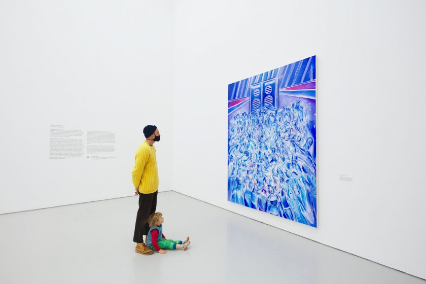 A photograph of a man and small child in a bright white gallery looking at the Denzil Forrester painting Itchin & Scratchin, a vibrant blue painting of bodies moving to music in a nightclub.