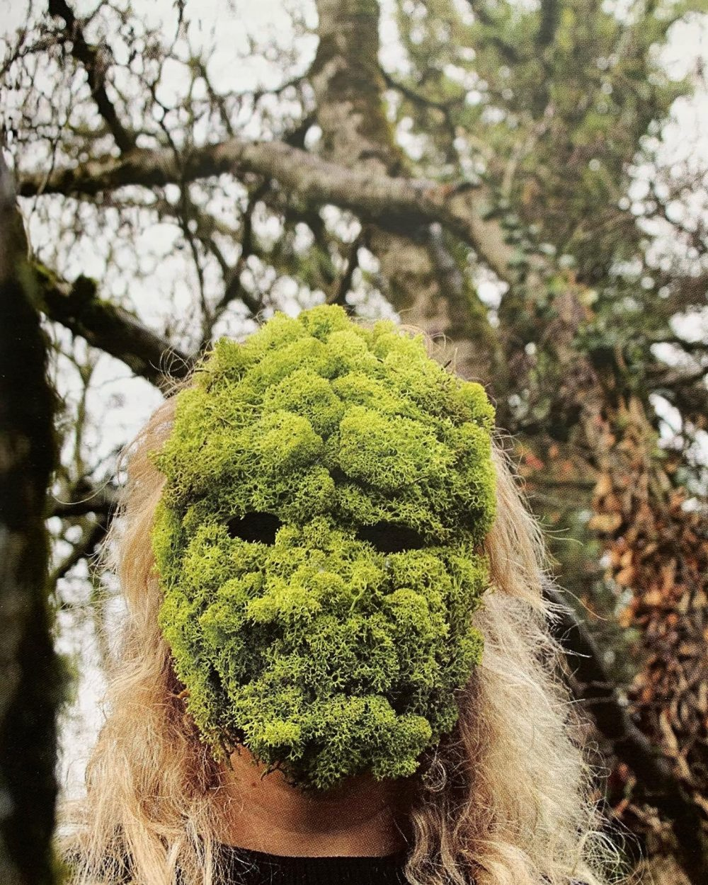 Annabel Pettigrew. A grainy colour photograph of a person with long light blonde hair, positioned in a forest setting, with a mask over their face made from bright green moss.