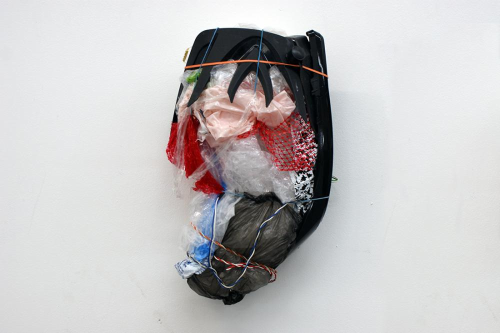 Ben Hartley. an oval-shaped sculpture comprising of pink and grey plastic bags, clear bubble wrap; blue, white, and red wire, clear tape, red netting and other unidentified objects hung on a white wall