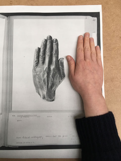 Eleanor Duffin. A person's right hand is placed alongside and on top of a black and white photocopy of a drawing of a left hand of the same scale.