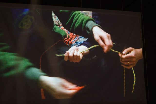 Jo Ball. An image of a video work in which two figures are holding and passing various pieces of colourful rope between themselves