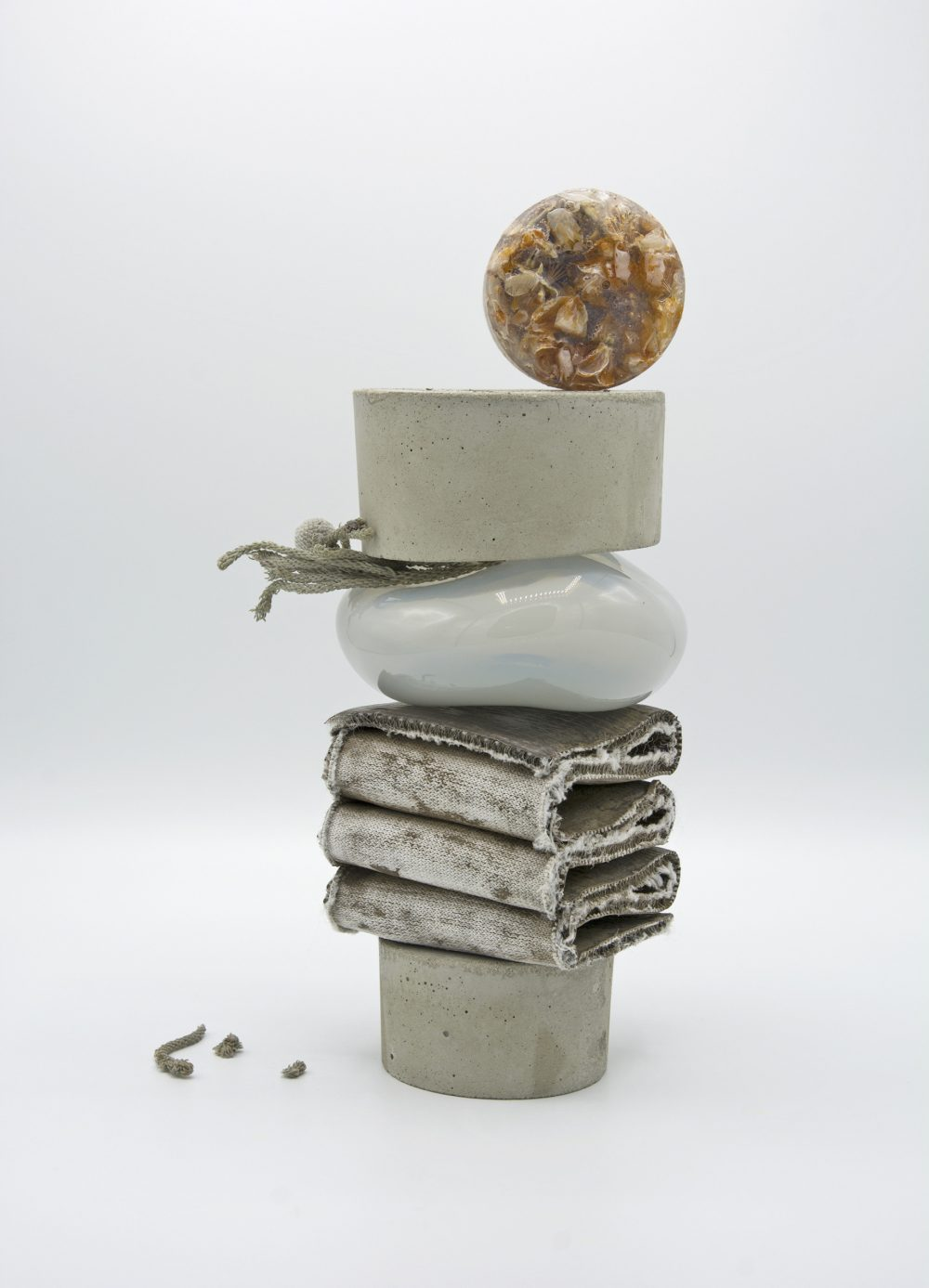 Kelly O'Brien. On a white background, a tall stack of forms including two concrete discs, a strip of hessian/clay material folded into a ripple, a glass-like smooth pearlescent form, and a disc balanced on the top of the stack which looks like shells and other mixed matter set into a resin disc.
