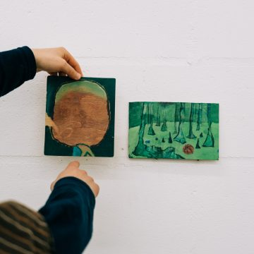 A photograph in Isaac Jordan's studio where he positions two small paintings on hard board