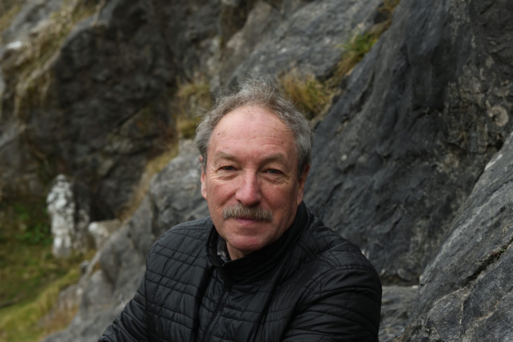 A white man with grey hair and moustache, wearing a black puffer jacket sits in front of grey rock forms with his hands in his pockets.