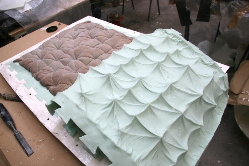 A studio process revealing a light brown dyed quilted cushion being de-moulded