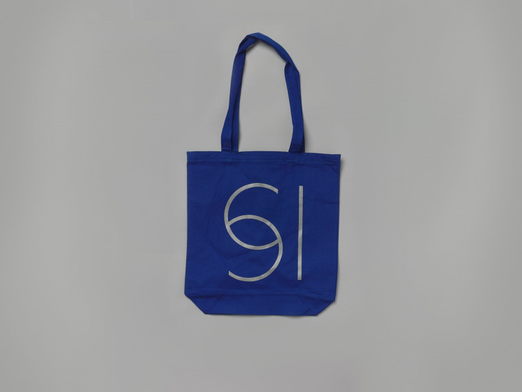 A photograph of a blue tote bag against a grey background