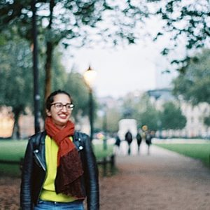 a woman wearing a red scarf, yellow sweater and leather jacket smiling and walking in a park