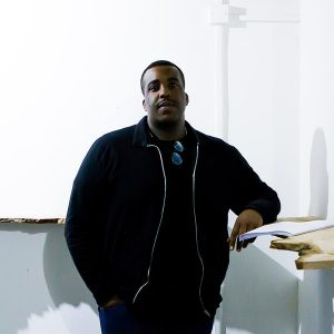 a man wearing a black t-shirt and black jacket, leaning on a shelf