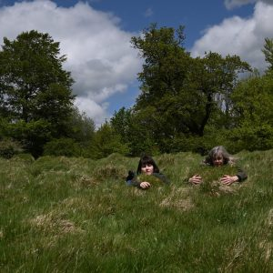 two women partially submerged in a large mound of grass