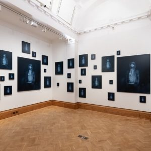 a gallery space with different sized black and blue paintings on the wall