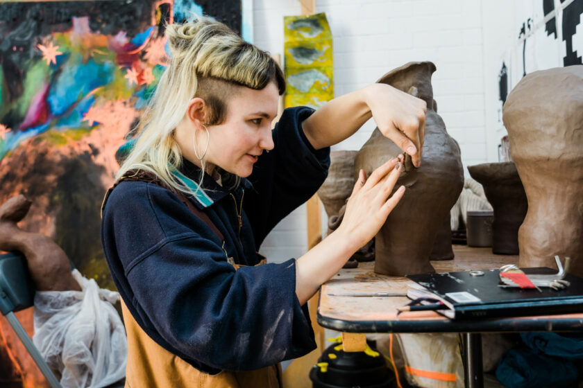 A photograph of artist Izzy Mooney in her studio at Spike Island