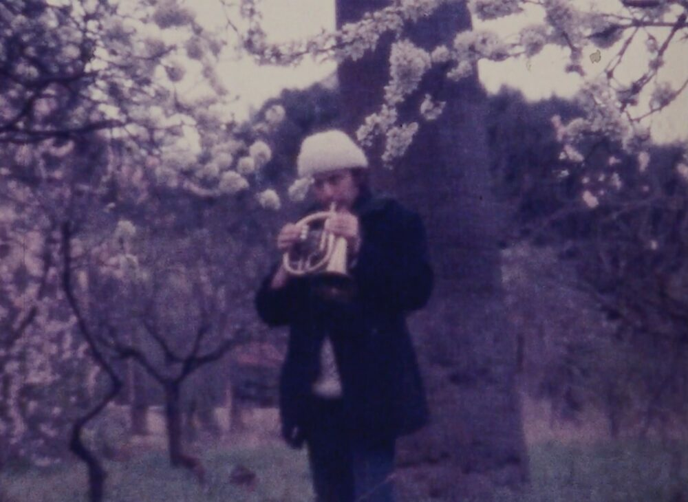 Film still of a man playing a small brass instrument in front of a blossom tree, wearing a white woolly hat
