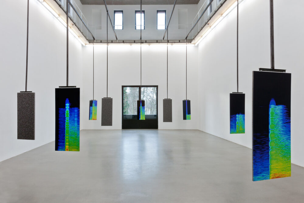 An installation view of multiple portrait orientation digital screens suspended in a gallery space from long black bars leading to the ceiling above. Each screen shows visualized sound frequencies in bright blues, greens and orange colours.