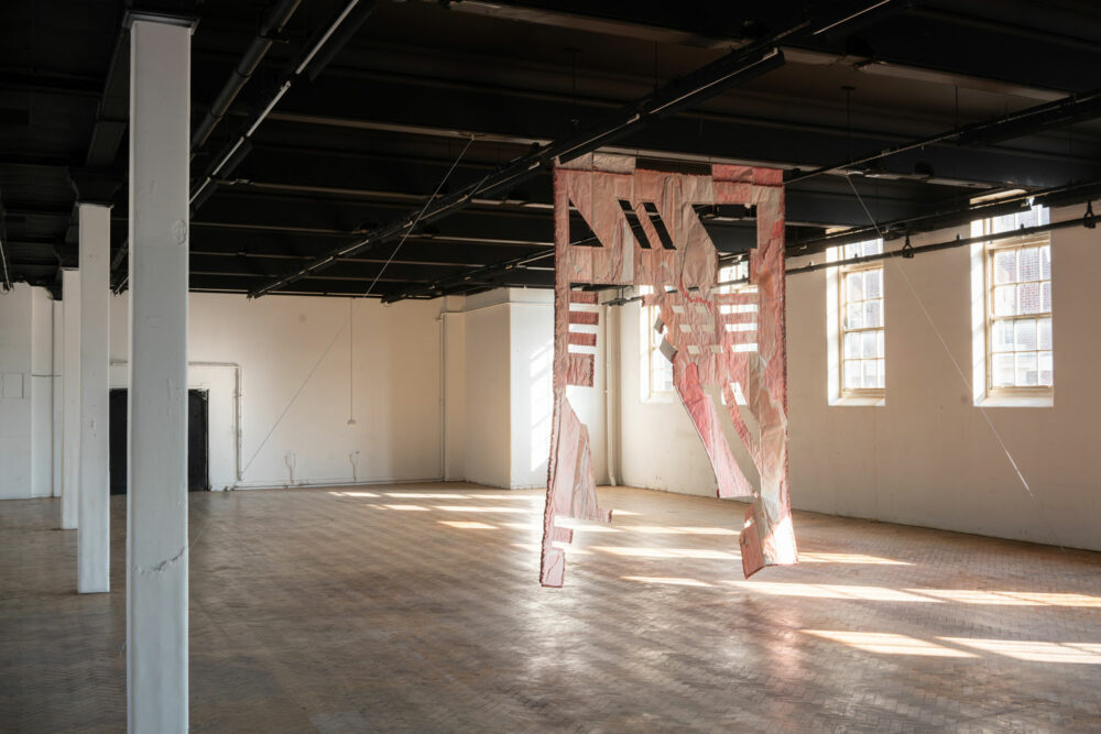 A large light pink flag with geometric cut-away panels hanging in a large empty room with wooden floor.